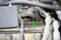 Unplug the last injector connector on the left side by pushing on the retaining clip (green arrow) and pulling up on the connector.