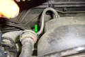 At the back on the right side of the fuel rail remove the fuel pressure regulator vacuum line (green arrow) by twisting it first then pulling it off the regulator port.