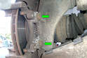 Remove the two 16mm fasteners (green arrows) that mount the caliper brake to the rear spindle.