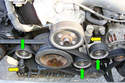 AC and Drive Belt Tensioner Removal Eight Cylinder - Working at the front of the eight cylinder engine identify the three drive belt pulleys (green arrows) and the two tensioner devices (yellow arrows).