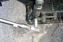 Remove the lower tensioner mounting nut and pull the tensioner off of its support bracket.