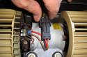 Unplug the motor by squeezing the two tabs of the electrical connector and pulling it straight up.