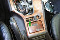 Remove the Phillips head fastener (green arrow) in the hazard switch opening of the shifter trim panel cover
