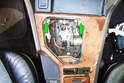 Remove the two Phillips head fasteners (green arrows) at the front of the center console inside the shifter opening that secure the shifter trim panel to the center console.