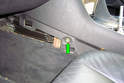 With both carpeted panels out of the way remove the two 7mm fasteners (green arrow) in the side of the center console towards the front.