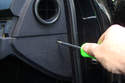 There is a Phillips tip screw that is mounted under a rubber cover in the side panel of the dash.