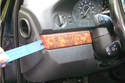 On the left side of the steering column you will have to lever off the wood trim panel with a plastic pry tool.