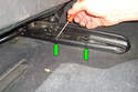Use a pick tool to unclip the two plastic tabs (green arrows) that hold on the seat rail cover.