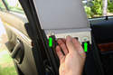 To remove the upper B-pillar, pull the bottom of the upper B-pillar trim panel away from the body to detach the retaining clips (green arrows).