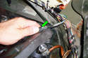 Unhook the wiring harness from the tab (green arrow) on the bulb housing.