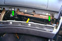 With the center dash panel out of the way two Phillips screws (green arrows) are exposed and need to be removed.
