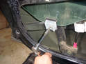 Loosen the second fastener towards the rear of the door and pull the clamp and the rubber off the glass if you can.