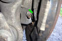 This photo illustrates the front of the rear spindle inside the wheel well at the ABS wheel speed sensor (green arrow).