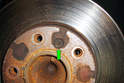Locate the 5mm Allen head screw (green arrow) used to secure the rotor to the axle flange.
