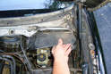Pull the lower cover out by maneuvering it in between the wiper transmission and the brake booster