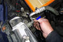 Working at the right side of the radiator squeeze the locking tab of the radiator temperature sensor and pull the connector in the direction of the blue arrow.