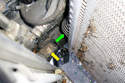 Working at the right side of the radiator we see the mounting pin (green arrow) is hidden by the radiator tank.