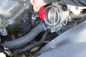 Working at the thermostat side of the lower radiator hose use a flat head screwdriver to loosen the clamp that secures the lower coolant hose with the thermostat.