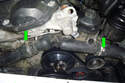 Working at the front of the engine loosen the two hose clamps (green arrows) that connect the thermostat housing to the upper and lower radiator hoses.
