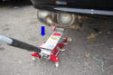 Lower the jack and allow the muffler to drop down in the direction of the blue arrow.