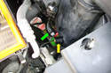 Separate the lower hose of the expansion tank (green arrow) from the port on the bottom of the expansion tank.