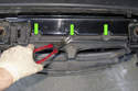 Working at the top of the radiator duct, remove three Christmas tree style push in clips (green arrows).