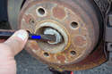 Use a straight edge drift chisel and tap in the direction of the blue arrow to gradually open the pinch of the nut on the axle shaft.