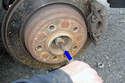 Working back out at the rear rotor use a drift punch to tap out the axle shaft from the hub and spindle it sits in.