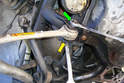 Loosen but do not remove the 16mm bolt and 18mm nut that secures the lower control arm inner bushing to the sub-frame.