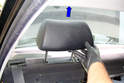 Working at the rear parcel shelf remove the rear head rests by pulling straight up on them in the direction of the blue arrow and removing them from their mounts.