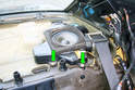 Working at the left side speaker enclosure remove the two Phillips head screws that mount it to the body of the car.