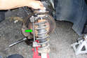 Use a spring compressor (green arrow) to compress the strut spring on one side of the strut.