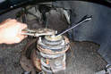 At the top of the strut assembly secure the strut rod with an open ended 6mm wrench.