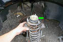 Remove the washer (green arrow) from the top of the strut mount.