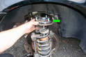 Remove the upper strut tower mount (green arrow) from the strut assembly.