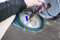 Use pliers to twist back and forth on the fuel line hose while moving it in the direction of the blue arrow.