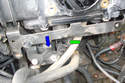 Reach behind the bracket on the intake manifold below the throttle body and push on the electrical connector retaining clip (green arrow) and unplug it by pulling the connector in the direction of the blue arrow.