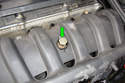 With a 19mm socket remove the positive terminal bolt (green arrow) from the intake manifold.