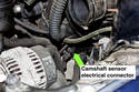 The camshaft sensor electrical connector is located below the throttle and behind alternator.