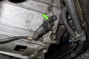 The crankshaft sensor is located at the bottom of the transmission bell housing on the right side.