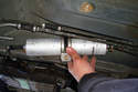 Give the fuel filter a twist to break it loose from the hoses and pull out the hoses.