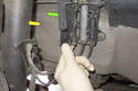 Working behind front strut (yellow arrow), open plastic door (green arrow) for ABS sensor electrical connector.