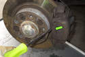 Using a flathead screwdriver, remove brake caliper anti-rattle spring (green arrow) by prying out while securing with hand.