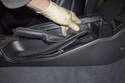Working in the vehicle interior, pull the rear of the parking brake handle trim cover off.