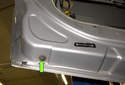 Working at the bottom of the door, remove the 10mm window guide fastener (green arrow).