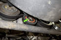 The tensioner on the A/C belt is secured in position using a locking bolt (green arrow).