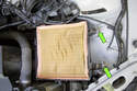 Next, you have to loosen two 10mm nuts about 10 turns from the lower air filter housing (green arrows).