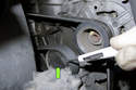 Using a small flathead screwdriver, remove the tensioner dust cap.