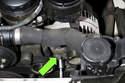 Working at bottom of alternator, loosen lower alternator mounting bolt (green arrow).