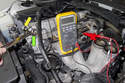 In this photo the wrench (green arrow) is close to the sensor (yellow arrow), so the DVOM reads about 0 volts.